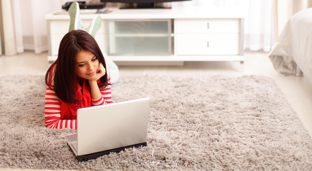 Portrait of dreamy smiling young woman using laptop while lying on floor at home